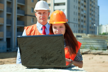 Two architects wearing protective helmet works in front of building site photo