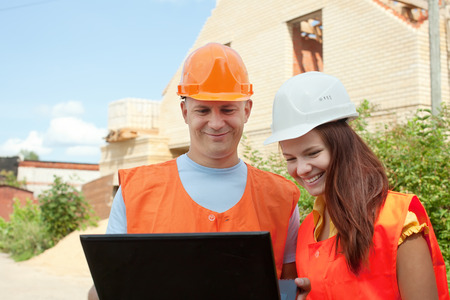 Portrait of two builders works at building site
