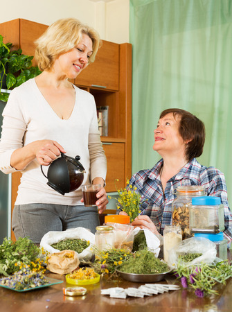 Two cheerful seniore women sitting at the table with herbal tea and herbs photo