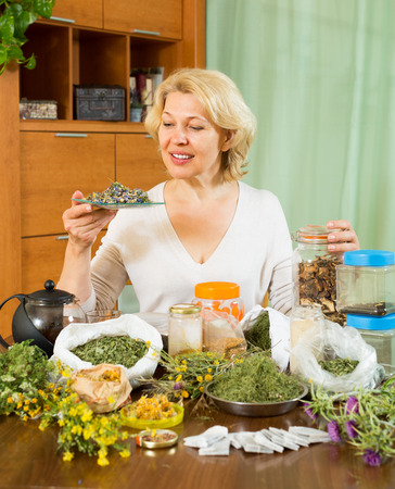 Smiling aged woman sitting at table with aroma herbs in home photo