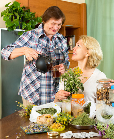 mature women: Happy mature women relaxing at home and drinking herbal tea