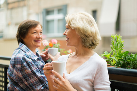 Two mature housewives drinking tea at terrace with decorative plants photo