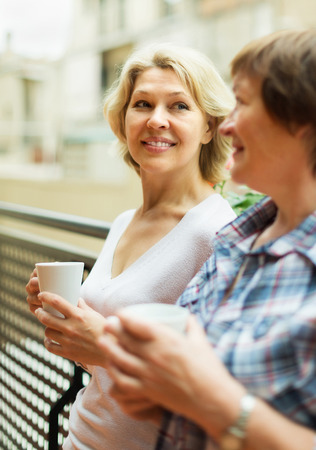 Two cheerful mature women drinking tea on balcony and smiling photo