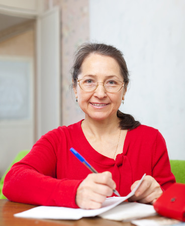 mature woman counts the family budget at  home