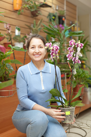 Happy mature woman chooses Phalaenopsis orchid in pot at flower shop photo