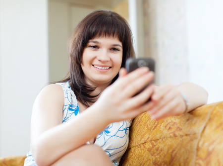 ordinary woman: ordinary woman sends SMS by mobile in home