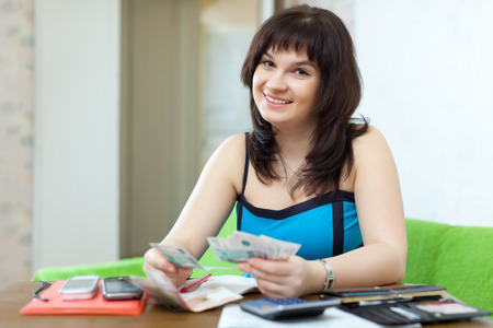 helps: Housewife calculates the family budget at  home