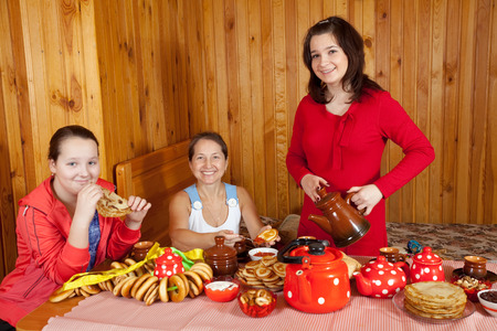 banket: Happy mother with teenager daughter eating pancake with caviare during  Maslenitsa festival Stock Photo