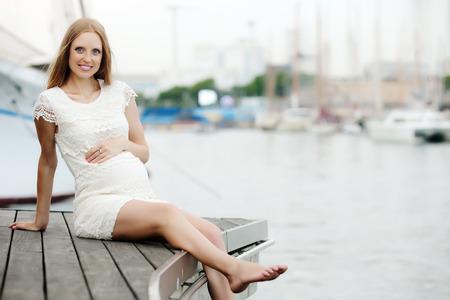 gravida: Happy pregnancy woman sitting near sea port Stock Photo