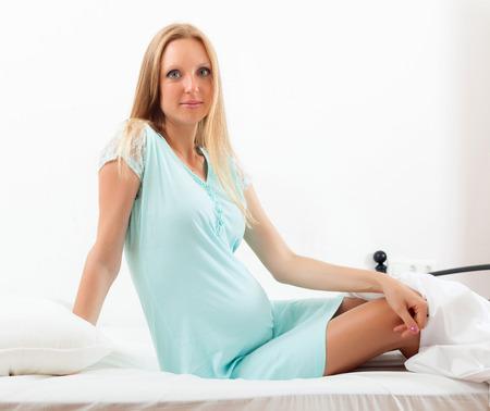 Pretty pregnancy woman in blue  nightdress in  bed