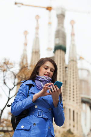 Young girl calling by mobile against Sagrada Familia at Barcelona photo