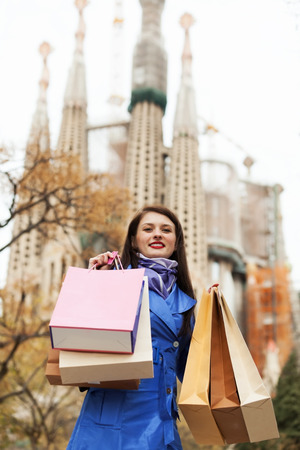 Smiling woman with shopping bags at street against Sagrada familia in Barcelona photo