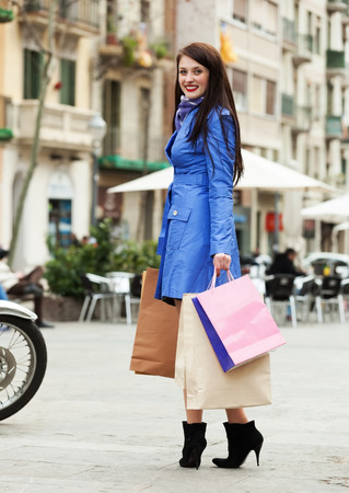 Young woman with shopping bags at street photo