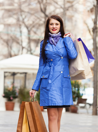 happy woman in blue cloak with shopping bags at street photo