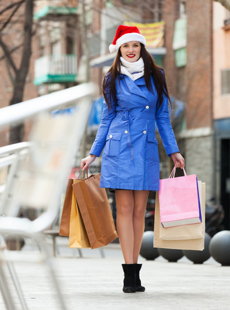 Girl in coat  with purchases at street during the Christmas sales photo