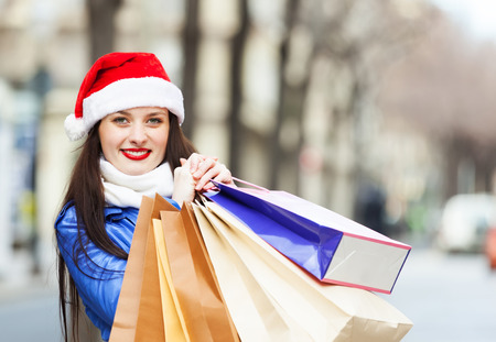 Happy girl with shopping bags at street during the Christmas sales photo