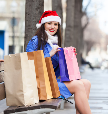 Smiling girl with purchases in city during the Christmas sales photo