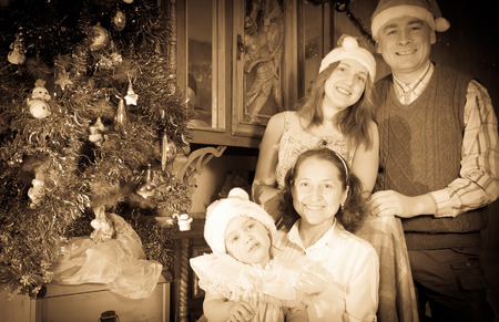 Vintage image of happy family of three generations with  Christmas tree at home  photo