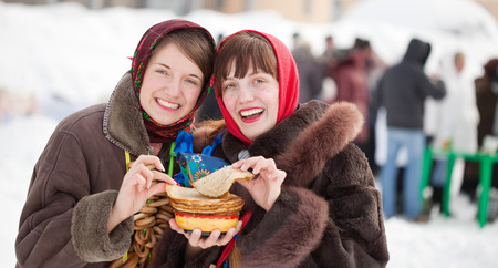 Girls in traditional  clothes tasting pancake  during  Shrovetide Stock Photo - 29092917