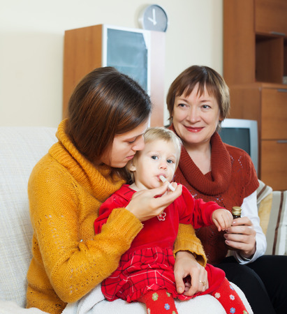 Young  mother with mature grandmother caring for sick toddler  photo