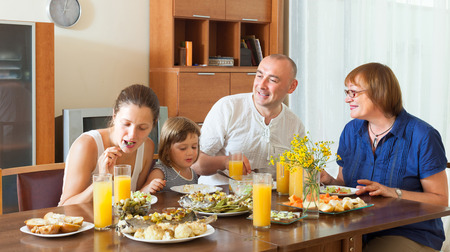 Smiling multigeneration family communicate over healthy holiday table