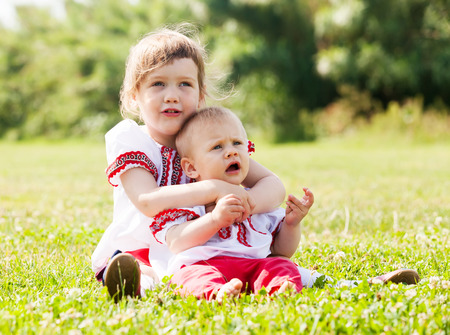 Two happy children in russian folk clothes on  meadow photo