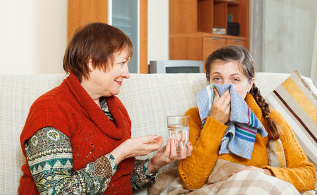 Mature woman caring for  adult daughter has cough in living room. Focus on girl