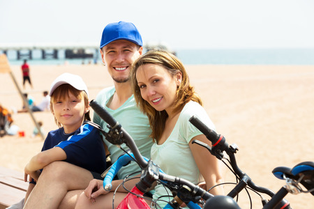 Smiling family having rest after cycling on sandy beach photo