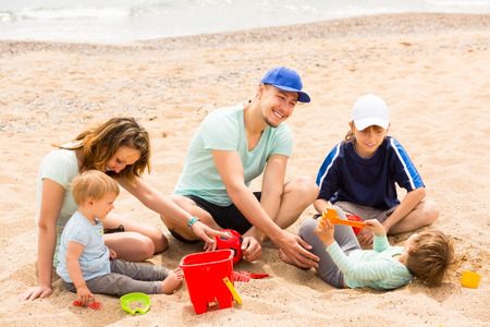 Happy parens with kids having a rest on sandy beach photo
