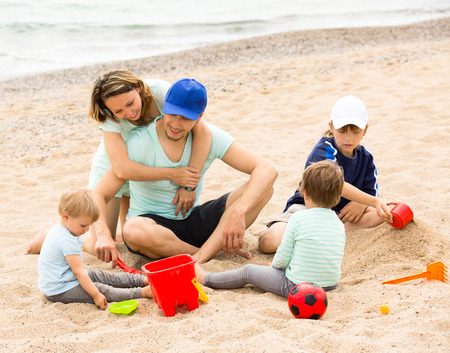 Happy parents and kids toying with sand at sea shore photo