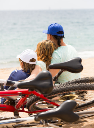 Couple with son sitting on sand with bicycles at seashore and looking on sea photo
