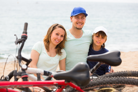 Family with teenager son sitting at seashore in summer day with cycles photo
