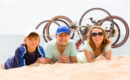 Positive parents with son lying on sand with bicycles at seashore photo