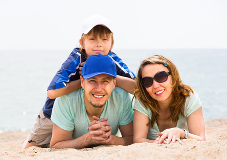 Happy middle-class family with son in casual at sandy beach photo