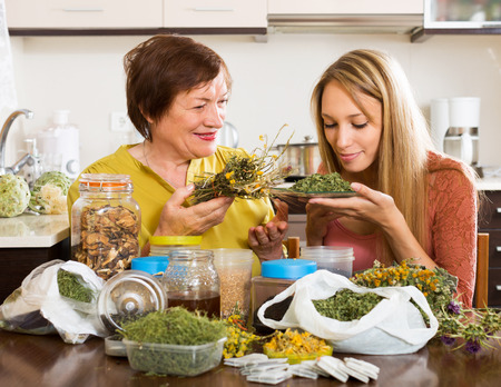 medical herbs: Happy  womans  with medicinal herbs brewing herbal tea