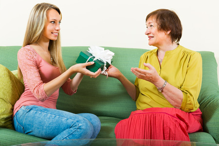 congratulating: Girl congratulating aged mother and giving a present on Mothers Day