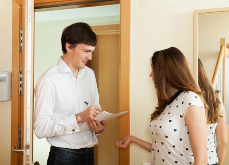 empleada domestica: Mujer que habla con la sonrisa del hombre con el papel en la puerta