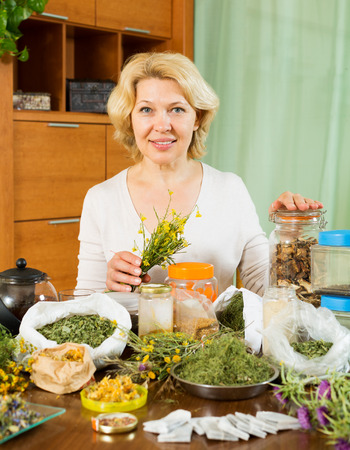 concoct: mature woman doing herbal tea and smiling at home