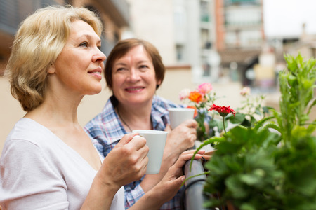 Two happy female pensioners drinking tea on balcony and smiling