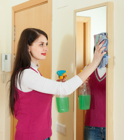 cleanser:  woman cleaning  mirror  with cleanser at home