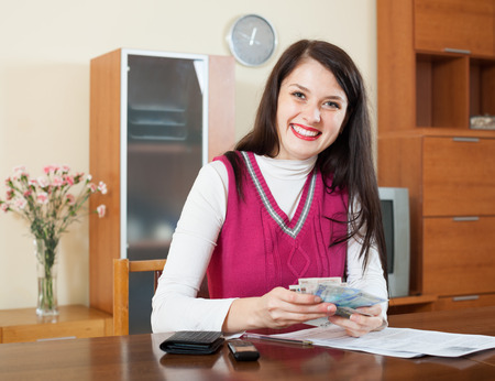 Happy brunette woman calculating the family budget at  home photo