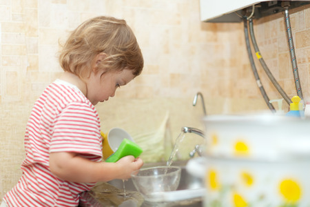 Baby girl washing dishes in kitchen photo