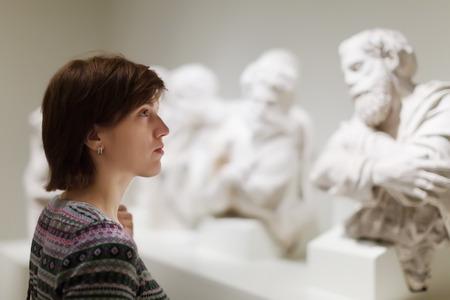 art museum: Giovane donna in cerca di antiche sculture in museo d'arte