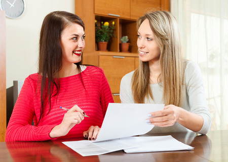 home office interior: Pretty girls with  documents  at table in home or office interior