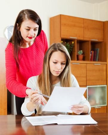 home office interior: serious women with financial documents at table in home or office interior