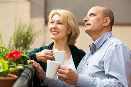Happy mature couple having morning coffee at balcony and smiling photo