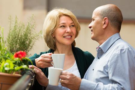 Smiling senior mature couple drinking tea and chatting on balcony photo
