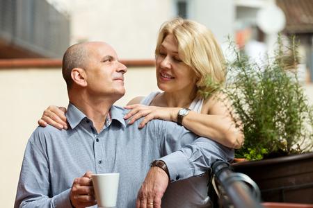 Positive elderly  couple having morning coffee at balcony  photo