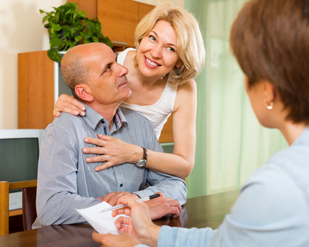 empleada domestica: Pares maduros mayores que en la mesa de llenado de cuestionario para los empleados