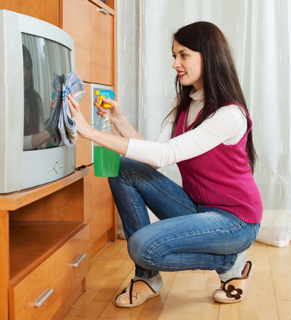 cleanser: Brunentte woman cleaning TV with cleanser at home